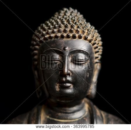 A Small Replica Statue Of The Head Of The Buddha Isolated On Black