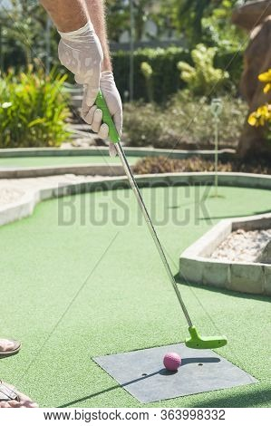 Man Teeing Off At Mini Golf Wearing Protective Gloves