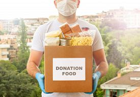 Coronavirus Donation Box. Delivery Food. Volunteer. Food Help. A Man In A Mask And Medical Gloves Ho