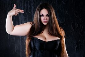 Angry Woman Showing Hand Gesture On Black Background