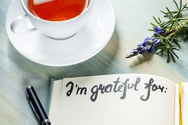Gratitude Journal With A Flower And A Cup Of Tea, With The Handwritten Phrase I Am Grateful For