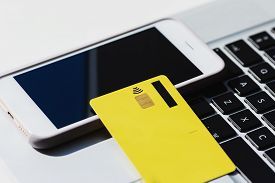 Yellow Credit Card, Laptop Keyboard, Smartphone On White Background