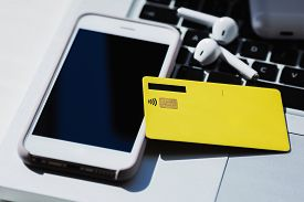 Yellow Credit Card, Smartphone Screen, Laptop Keyboard And Earphones Close Up
