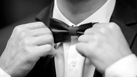 Close Up Of A Young Man Adjusting Tie