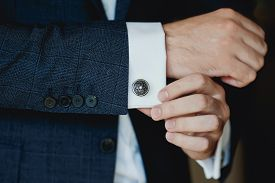 Close-up Of A Man In A Tux Fixing His Cufflink.
