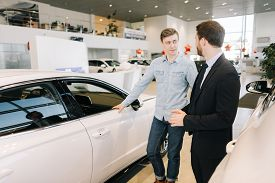 Young Handsome Man Preparing To Buy New Car In Auto Dealership. Professional Car Salesman Is Telling