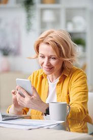 Happy blond woman with smartphone looking through working plan while sitting by desk in home environment during quarantine