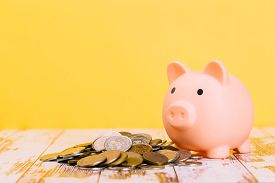 Pink Piggy Bank On Wooden Table And Yellow Background. The Concept Of Storage, Accumulation. Crisis,