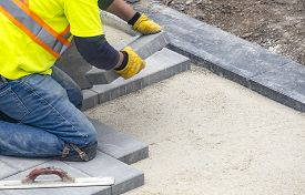 Workman In Safety Jacket Laying Patio Pavers In A Backyard