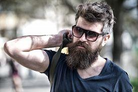 Bearded Man Carries Bag On Shoulder. Traveller Concept. Man With Long Stylish Beard Puts Bag On Shou