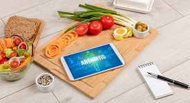 ARTHRITIS concept in tablet with fruits, top view