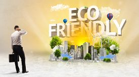 Rear view of a businessman standing in front of ECO FRIENDLY inscription, Environmental protection concept