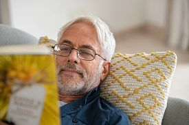 Happy mature man reading a book at home wearing eyeglasses. Senior man lying on couch wearing spectacles while reading novel. Close up face of old man reading book while relaxing at home, copy space.