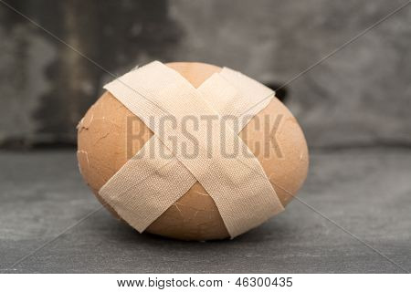 Broken Healthcare Concept Image Of Plaster On Egg