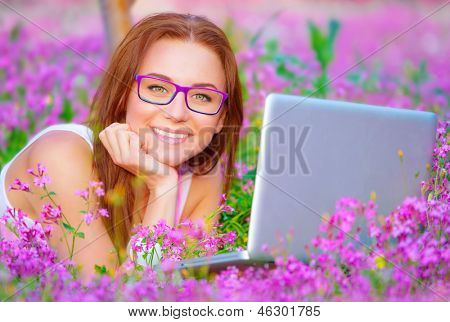 Closeup portrait of cheerful student girl lying down on purple floral field with laptop, wearing glasses, wireless internet, modern and technological lifestyle