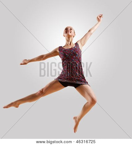 Girl dancing in a color dress with a gray background. isolate