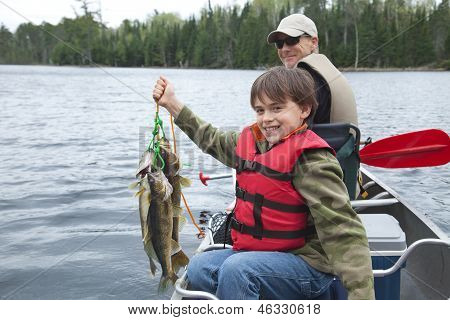 Young Fisherman Proudly Holds Stringer Of Walleyes