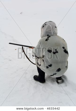 Hunter Squatted Down On Snow With A Rifle