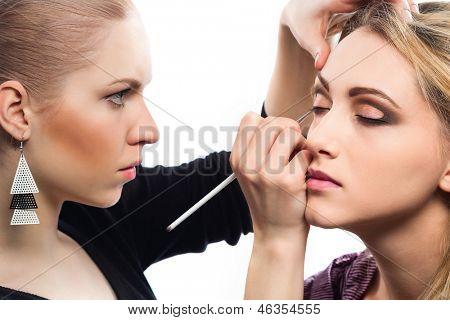 Backstage scene: Professional Make-up artist doing glamour model makeup at work