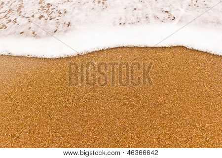 Close view of the small sea wave on the sand.
