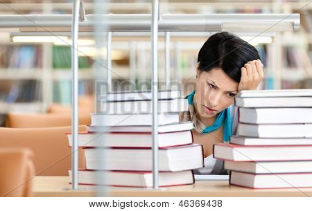 Sad female student is tired of training surrounded with piles of books sitting at the desk