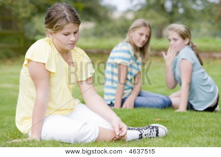 Two Young Girls Bullying Other Young Girl Outdoors