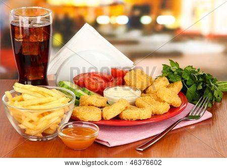 Fried chicken nuggets with vegetables,cola,french fries and sauce on table in cafe
