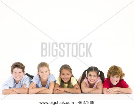 Row Of Five Friends Lying Down Smiling