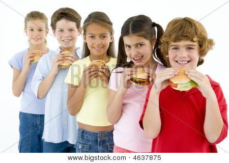 Row Of Five Young Friends Eating Hamburgers