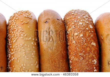 A closeup of 5 bagels standing on their sides with a white background. Bagels include, sesame seed, cinnamon raisin, mulit grain, and blueberry.
