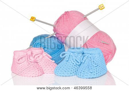 Knitted baby booties with blue and pink wool plus knitting needles, isolated on a white background.