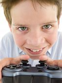 Studio shot of young boy on white background using videogame controller and smiling poster