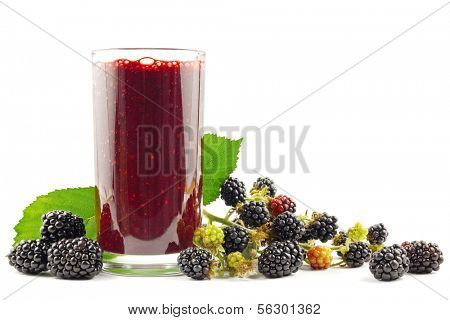 Glass with blackberry smoothie and blackberries on white