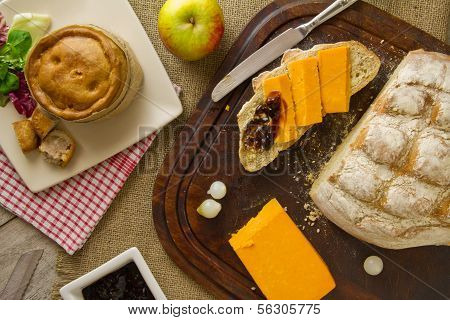 A typical ploughmans lunch fare spread out on burlap bread board and distressed boards. Melton Mowbray pork pie with artisan boule bread in basket next to red Leicester cheese butter salad and an apple. poster