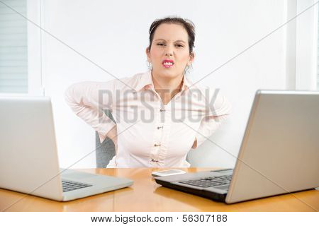 Young businesswoman having back pain while sitting at office desk