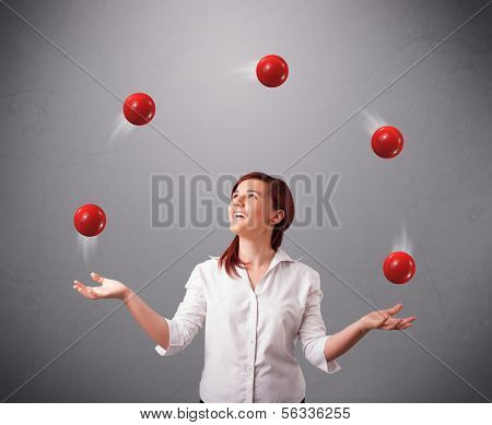 pretty young girl standing and juggling with red balls