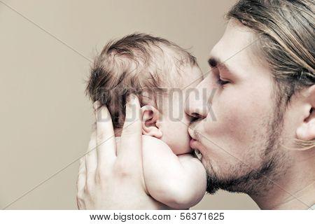 Vader met zijn jonge baby knuffelen en zoenen hem op de Wang. Ouderschap, liefde.