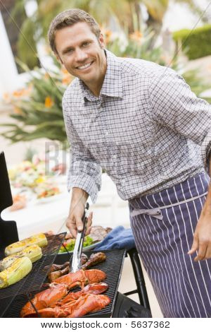 Man Barbequing In A Garden
