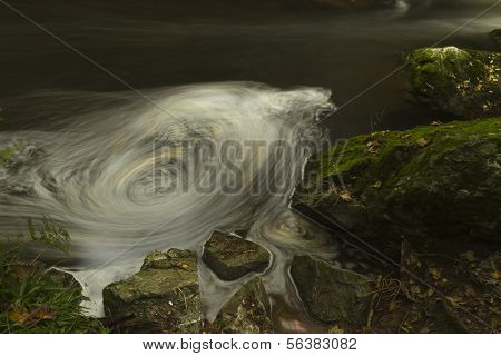 Apparent whirlpool appears in long exposure. The Dingle (Nant y Pandy) Llangefni Anglesey Wales United Kingdom. poster