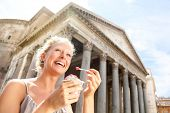 Girl eating ice cream by Pantheon, Rome, Italy. Happy tourist woman laughing enjoying Italian gelato ice cream while sightseeing travel landmark destinations in Rome. Beautiful blonde female model. poster