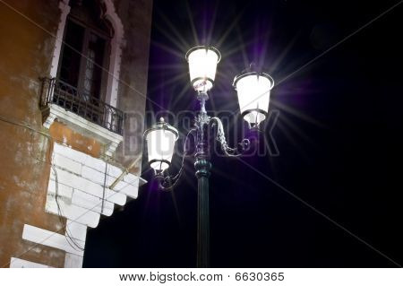 Lamps in venice with nice light beams and a house in the background poster