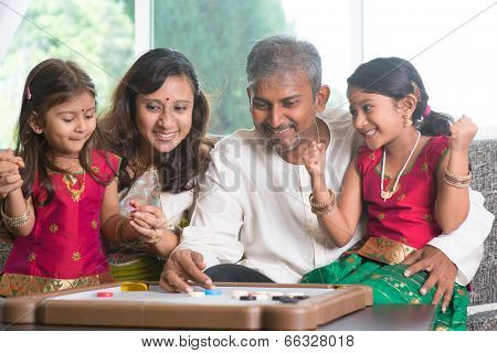 Asian Indian family playing carrom game at home. Parents and children indoor lifestyle.