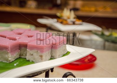 Malay colourful traditional dessert / kuih on a banana leave poster