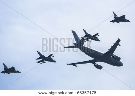 BERLIN, GERMANY - MAY 21, 2014: Airbus A310-304 is used as a tanker and fly two Tornado in refueling position, two outside flying Eurofighter are in waiting position, at ILA Berlin Air Show.