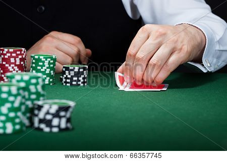 Human Hand Of Poker Player With Cards And Chips