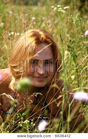 The Girl With Red Hair On A Meadow Among A Grass