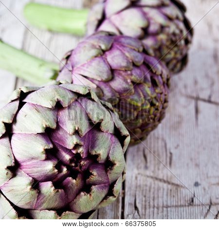 fresh artichokes closeup on rustic wooden background