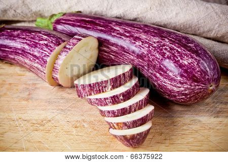 two fresh eggplants on wooden board