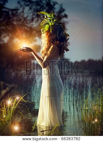 Fantasy girl taking magic light in her hands. Mysterious Night scene. Witch standing in the river and practice witchcraft. Fairytale