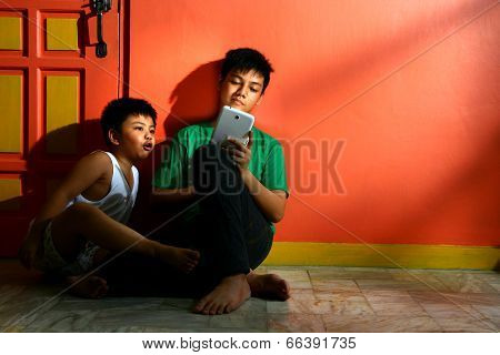 Young asian siblings with a tablet in a living room